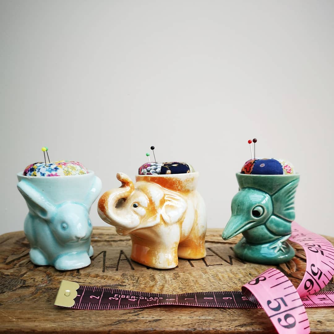 Three pincushions made in eggcups shaped like a rabbit, an elephant and a bird