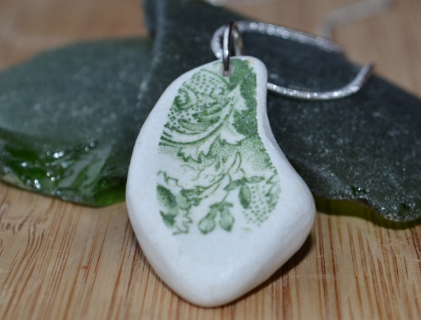 Necklace made from green and white beach pottery resting on green sea glass and driftwood