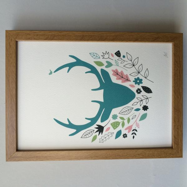 Printed illustration of stag head amongst leaves