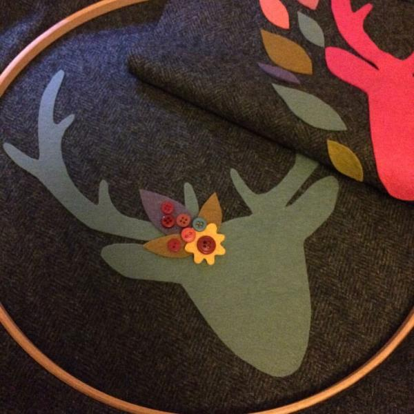 Embroidered textile illustration of stag head with flowers and leaves