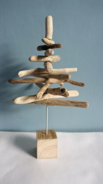 Tree made from pieces of driftwood against a green background